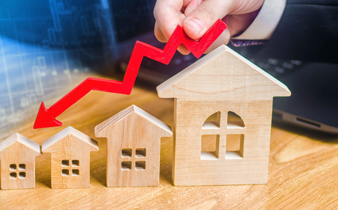 The hand holds a red arrow above the wooden houses down. The houses are decreasing. The concept of falling demand and supply in the real estate market. Economic crisis. The fall in prices.