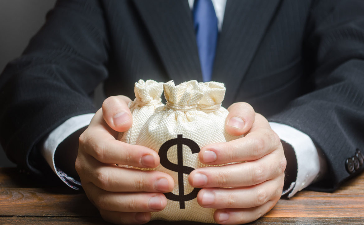 Businessman hugs US dollar money bags. Bank deposit. Budget management, tax collection. Trade, economics. Granting financing business project or education. Provision financial loan credit. Corruption